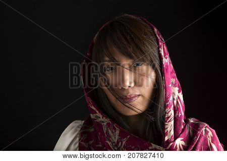 A close up low key portrait of a pretty Korean woman with a scarf.