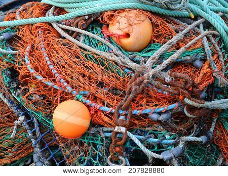 Close Up Pile of Fishing Nets and Buoys in Orange Green Blue and Rust