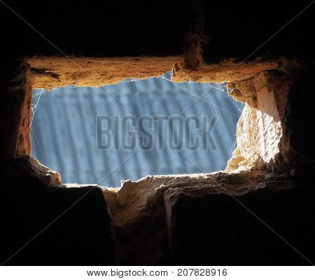 a hole in a brick wall overlooking the street