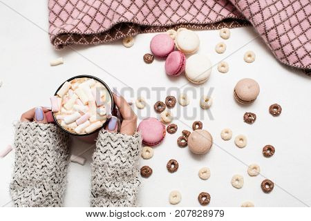 Sweet cold festive winter morning with latte and macaroons. Hot drink with marshmallow in hands of woman, colorful sweets around and partially seen plaid, top view