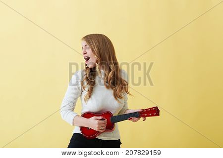 Attractive emotional young Caucasian woman in roll neck sweater singing passionately and playing ukulele. Beautiful woman singer playing musical instrument indoors. People music joy and fun