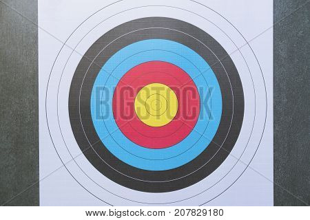 face view of an archery target over a black background sport and business success concept