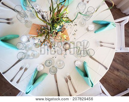 This is a wedding reception table setting from a beach themed wedding. It has a casual yet elegant feel with colors of turquoise and beige on white with a smattering of beach glass and pebbles.