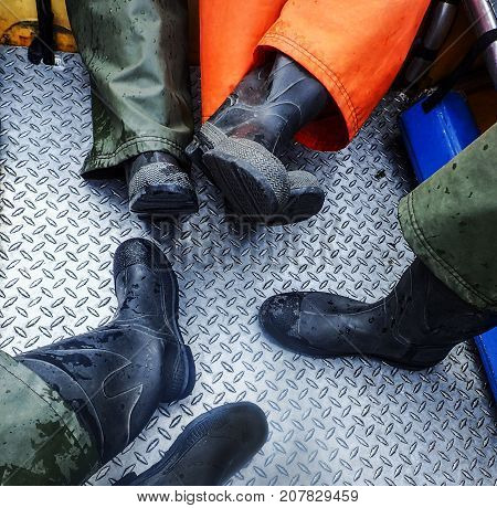 Group of Feet in Black Rubber Boots Relaxing on the Steel Floor of a Raft