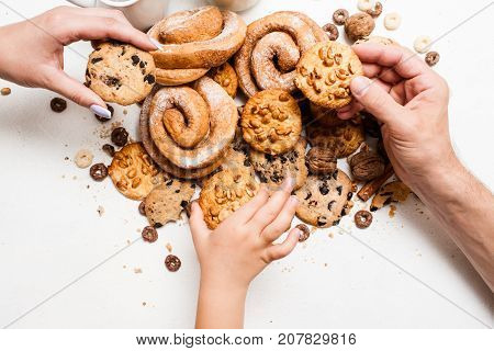 Healthy breakfast with pastry products, close up top view. Family taking wholegrain scones from mess of bakery food on table. Concept of home-baked shop