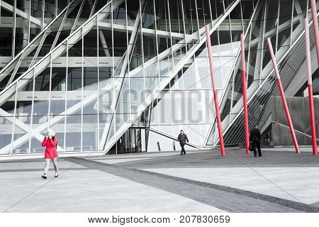 DUBLIN IRELAND - AUGUST 9 2017; Red color-splash on monochrome image, workers pass through on way to work architectural angles and patterns of Grand Canal Square a modern public space surrounded by modern architectural buildings and containing sculptures