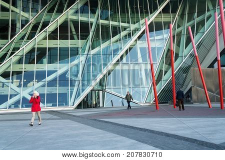 DUBLIN IRELAND - AUGUST 9 2017; Workers pass through on way to work architectural angles and patterns of Grand Canal Square a modern public space surrounded by modern architectural buildings and containing sculptures like the red poles known as Red Carpet