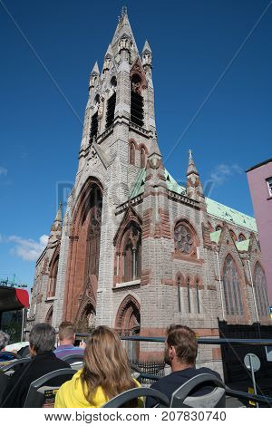 DUBLIN IRELAND - AUGUST 9 2017; Tourists on top deck of Hop on Hop off bus doing city tour pass a church while touring the city.