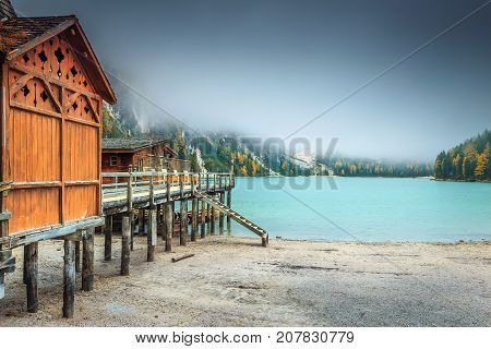 Stunning autumn misty landscape wonderful old wooden dock house on the lake with typical wooden boats Braies lake Dolomites Italy Europe