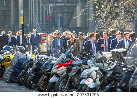 London, UK - March 15, 2017: City of London. Lots of business people in suits walking on the street. Modern busy business life concept.