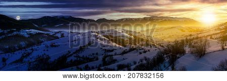 day and night time change concept in gorgeous panorama of mountainous countryside in winter. snow covered rural area on rolling hills and huge mountain ridge in a distance. fantasy world
