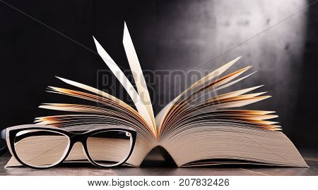 Composition With Open Book And Glasses On The Table