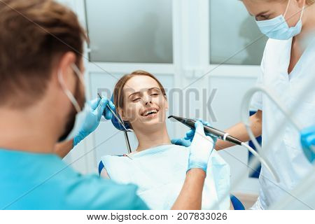 A young woman sits in a dental chair and smiles. Doctors bowed over her. They are going to treat her teeth