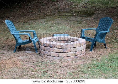 Stone fire pit and green lounge chairs in a backyard.