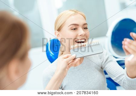 A female dentist determines the color of the patient's teeth. She holds a tooth color scale in front of the patient