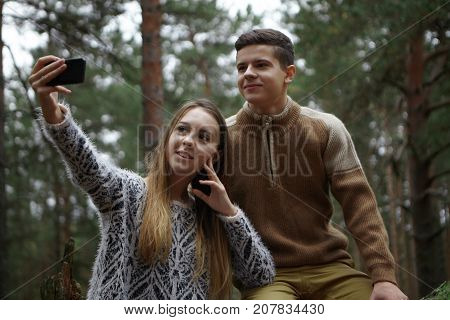 Happy siblings sister and brother taking selfie on mobile while hiking in woods. Beautiful young female holding smart phone taking self portrait posing in wild nature together with her boyfriend