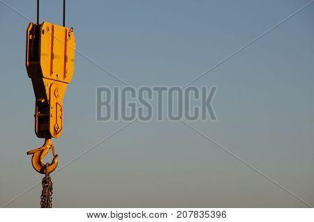 Der leuchtend gelbe Haken mit Flaschenzug eines grossen Baukrans
