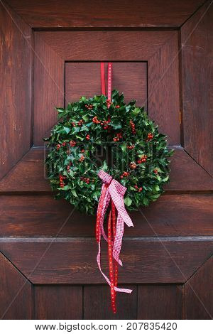 Christmas decoration of the door with a beautiful traditional wreath. Celebrating Christmas, decorating the house, family holiday.