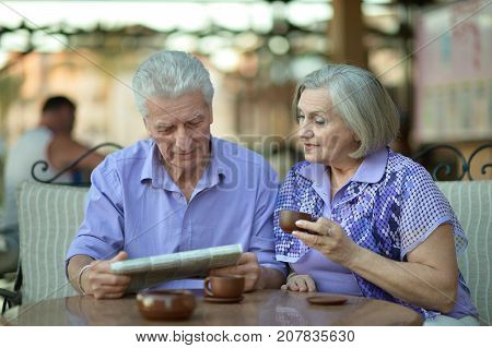 Senior couple drinking tea and reading newspaper  in outside in cafe