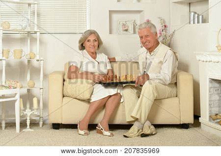 happy senior couple playing chess while sitting on couch