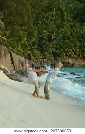 Happy elderly  couple  dancing  on  tropical beach