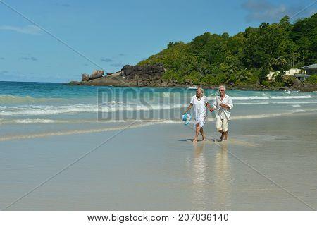 Happy elderly couple walking on  tropical beach