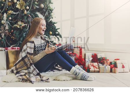 Surprised girl with laptop sitting at christmas tree background. Happy woman got greeting email from online shop with huge discount at winter sale. Holiday home atmosphere among gift boxes, copy space