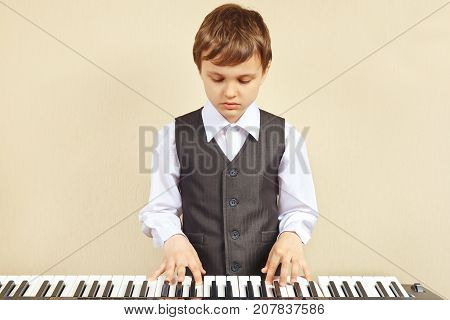 Little cut boy in a suit playing the electronic synthesizer