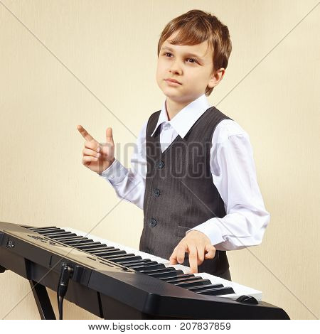 Little pianist in a suit playing the electronic piano