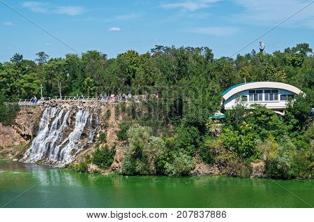 Dnipro Ukraine - August 08 2015: View of the green Dnipro river island with waterfall and a viewing platform on a clear sunny day