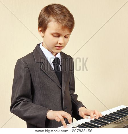 Little beginner musician in a suit playing the electronic organ