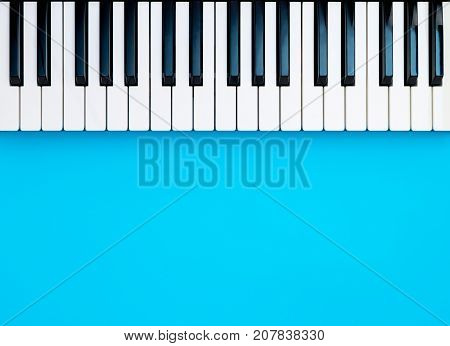 Music Synthesizer Piano Keyboard keys on blue copy space