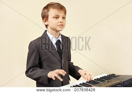 Young beginner musician in a suit playing the electronic organ