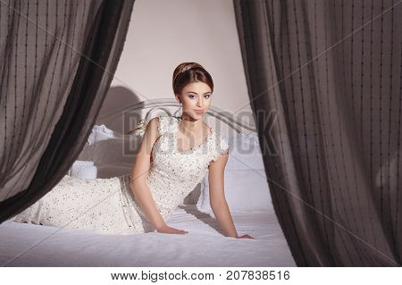 Beautiful Young Bride With Makeup And Fancy Hairstyle In Fancy Dress Sitting On Bed