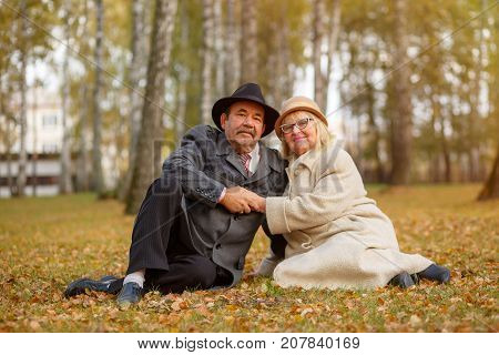 Mature couple sit on leaves in the autumn park