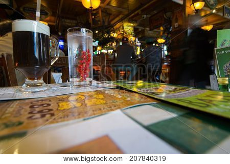 DUBLIN IRELAND - AUGUST 10 2017; Interior of typical Irish bar dark panelled walls dim light and two glasses on table containing water with red berries and Guinness Stout with characteristic white froth on table.