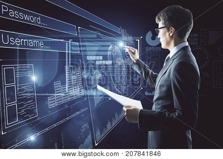 Side view of young businessman with document in hand drawing abstract digital business interface on dark blue background. Hologram concept. Double exposure