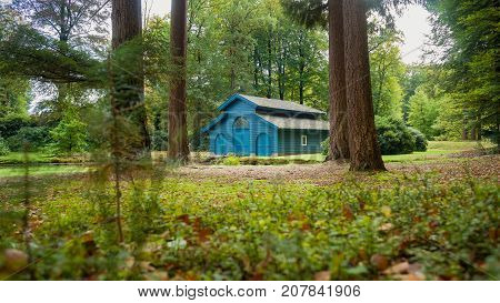 Old boat house in a tranquil ferny park with autumn leaves scattered over a charming water. A scene in the palace park 't Loo in Apeldoorn in the Netherlands