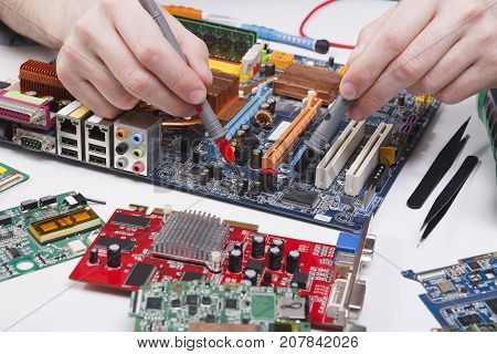 Engineer checking motherboard with multimeter close up. Computer diagnostics, maintenance support and repairing service concept.