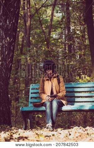 Young stylish hipster girl sitting on the bench in the autumn park and reading electronic book