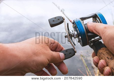 A man is fishing with a backcasting reel. Hands, a rod and a backcasting reel
