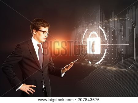 Side view of young businessman using tablet with abstract digital padlock hologram. Crime concept. Double exposure