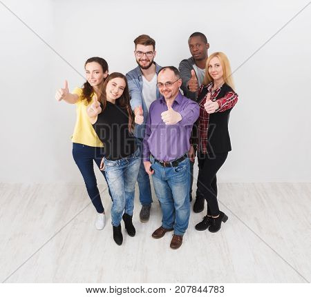Successful team show thumb up gesture. Confident successful young people are happy and satisfied, white background, top view
