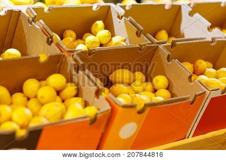 A huge boxes with lots of lemons. Yellow lemon in a wooden box in the store. Close-up of colorful vegetables. Food concept.
