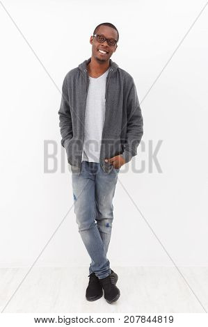 Cheerful young african-american man studio shot on white background. Smiling, relaxed and confident black guy wearing glasses