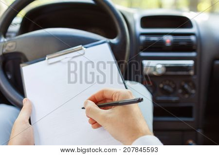 A young handsome man is sitting in the car and working. Men's hands hold a notebook and write something in a notepad. Close-up of hand with pencil. Business concept.
