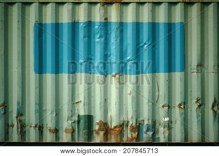 The side view of an old rusted cargo container with reworked and overpainted parts.