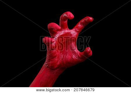 Painted in red color female hands make different shapes of fingers and palms against on a black background. Close-up of hand. Halloween concept.