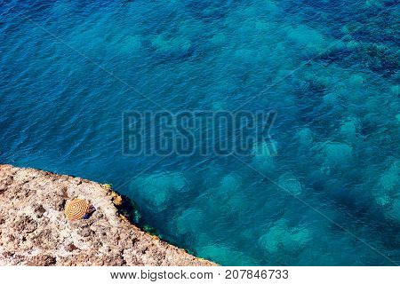 Beach with yellow red parasol and blue water