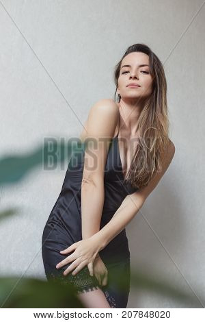 Vertical shot of young seductive mixed raced woman in black chemise looking straight down at the camera. Creative portrait of beautiful thoughtful lady posing indoors against white wall background.